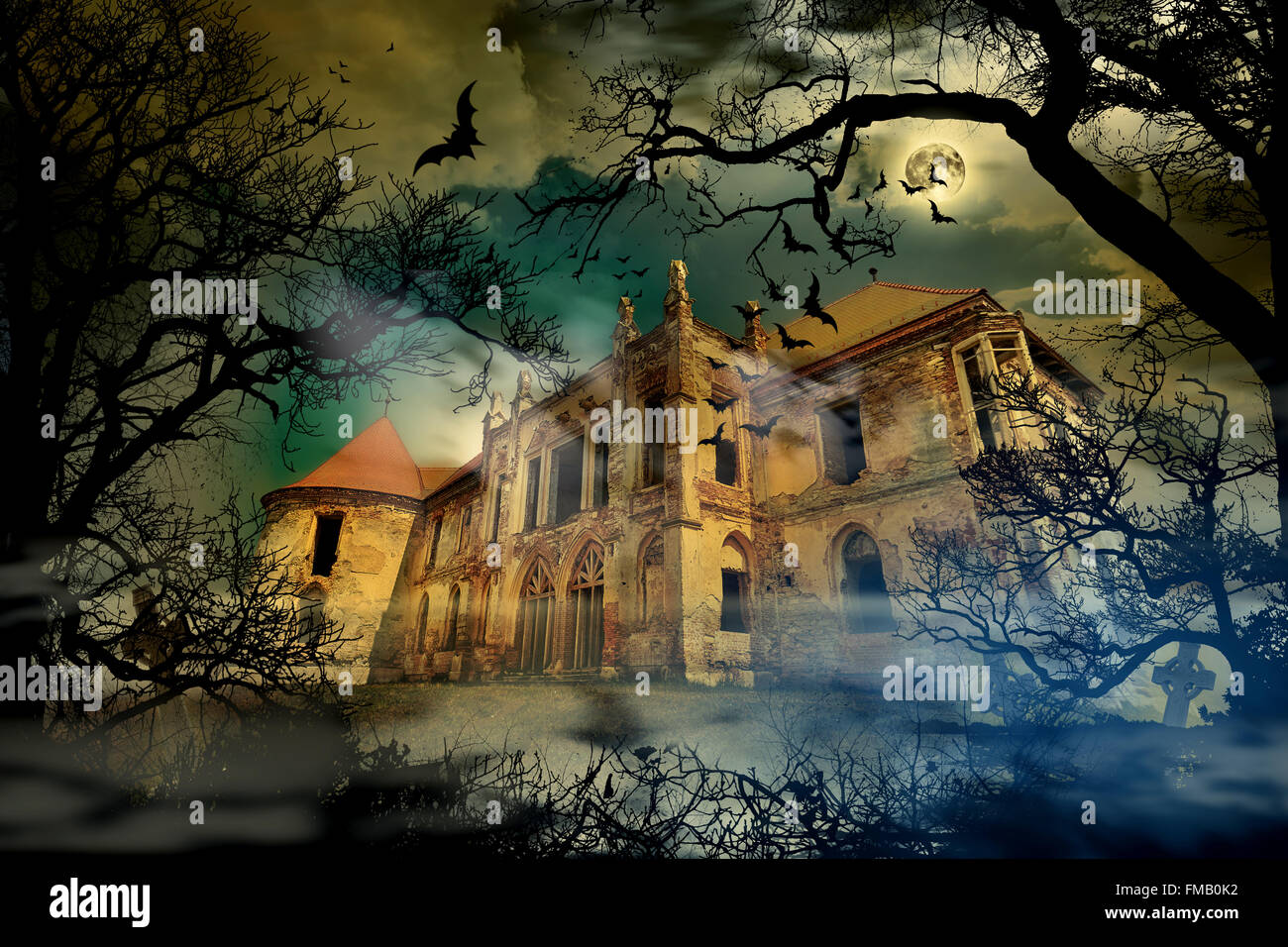 Haunted castle in creepy foggy background with tree silhouettes. - Stock Image