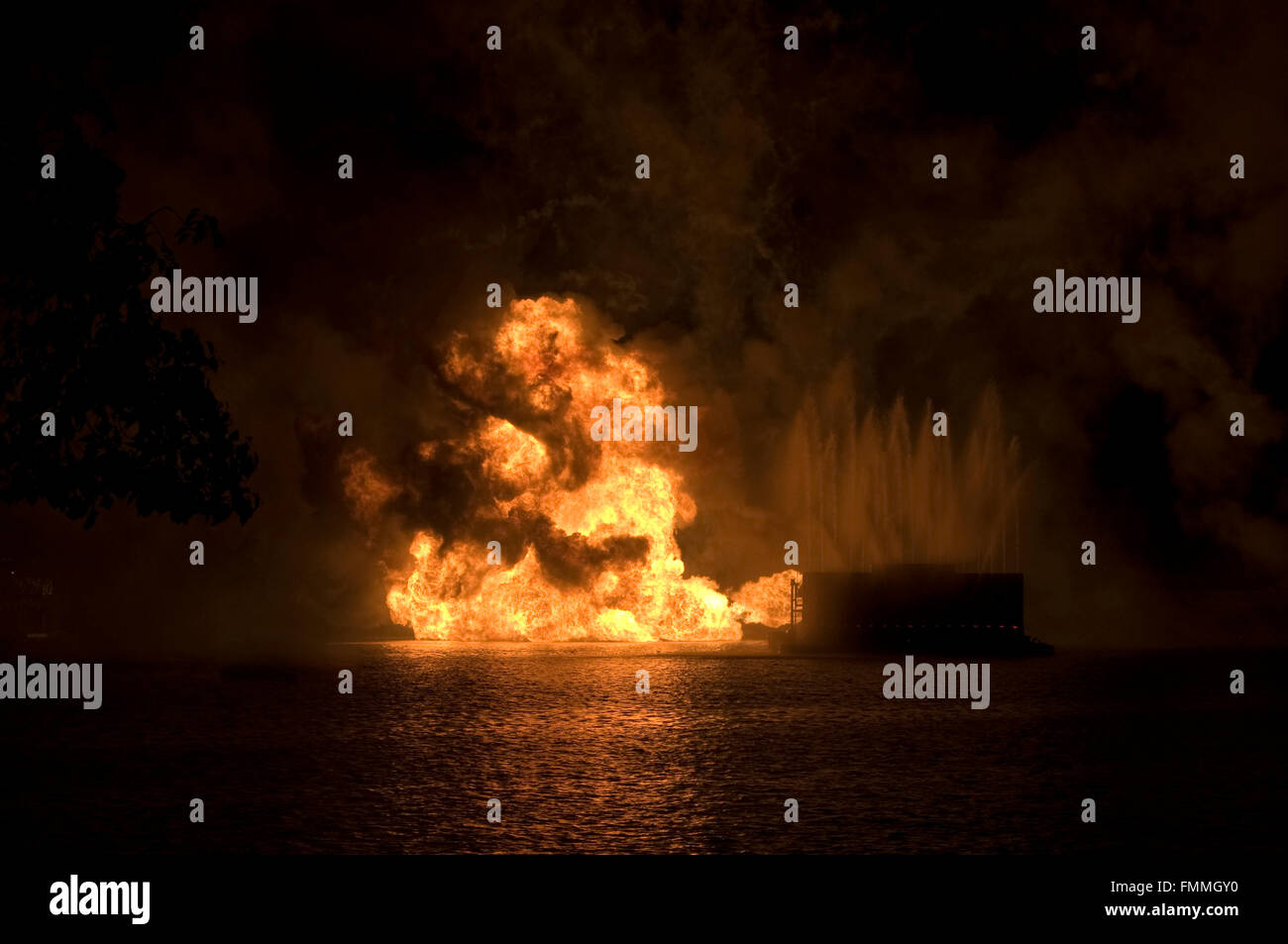 Gas fire explosion on water at night - Stock Image