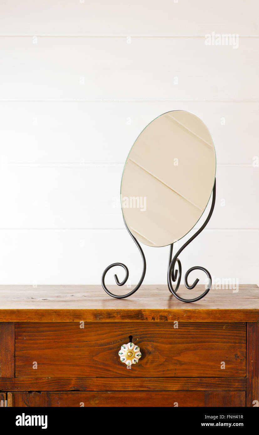 Retro mirror on bedside table,  background white wooden wall Stock Photo