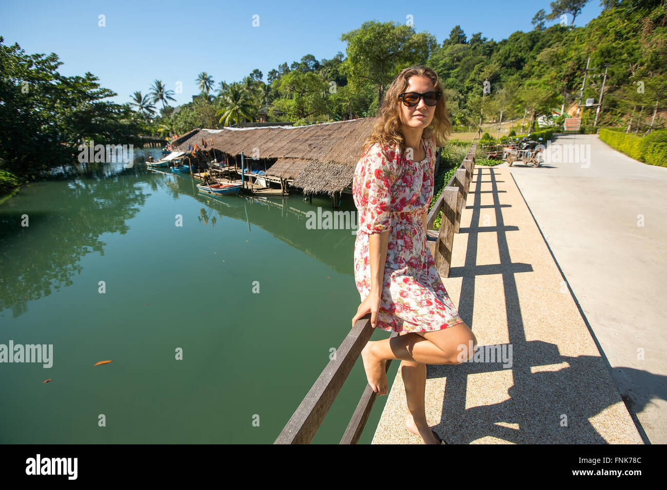 Young woman on the street in an Asian village. Journey. - Stock Image