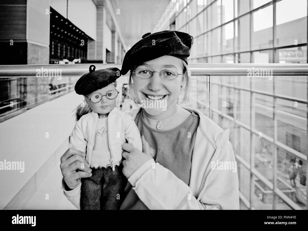 A little girl and her doll with matching berets in the airport (Logan Airport, Boston) excited about being on the Stock Photo