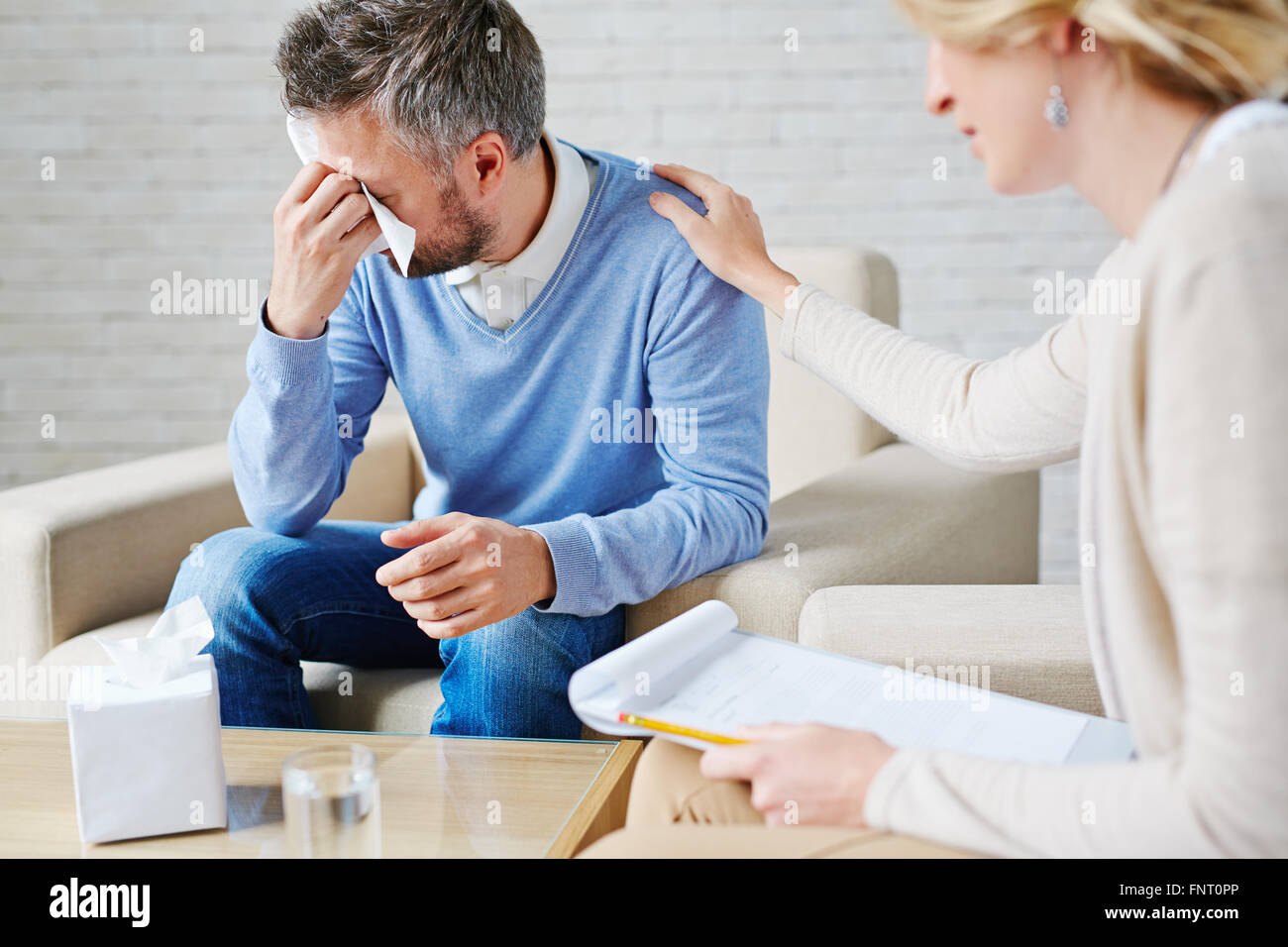 Depressed man crying while visiting his psychologist - Stock Image