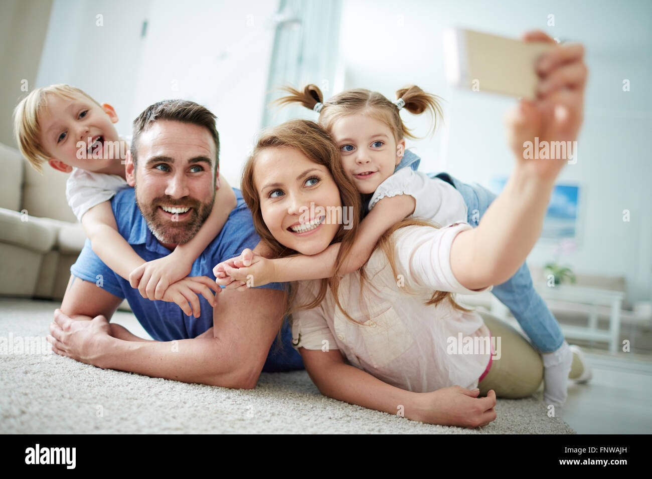 f0d7e47ba1c Happy young family taking selfie on the floor at home Stock Photo ...