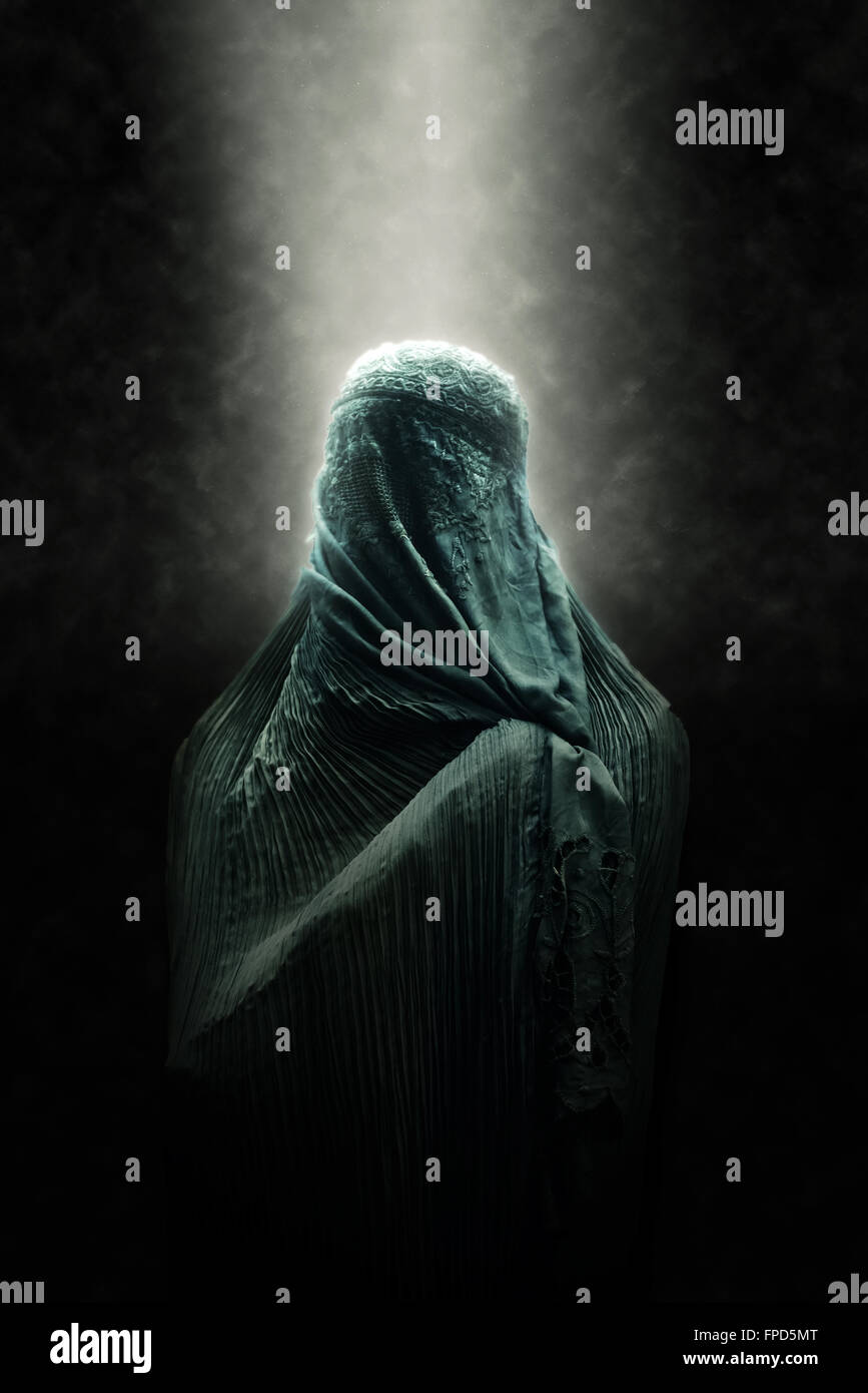 Veiled Islamic woman wearing a burka standing in a beam of overhead light in atmospheric darkness in a spiritual - Stock Image