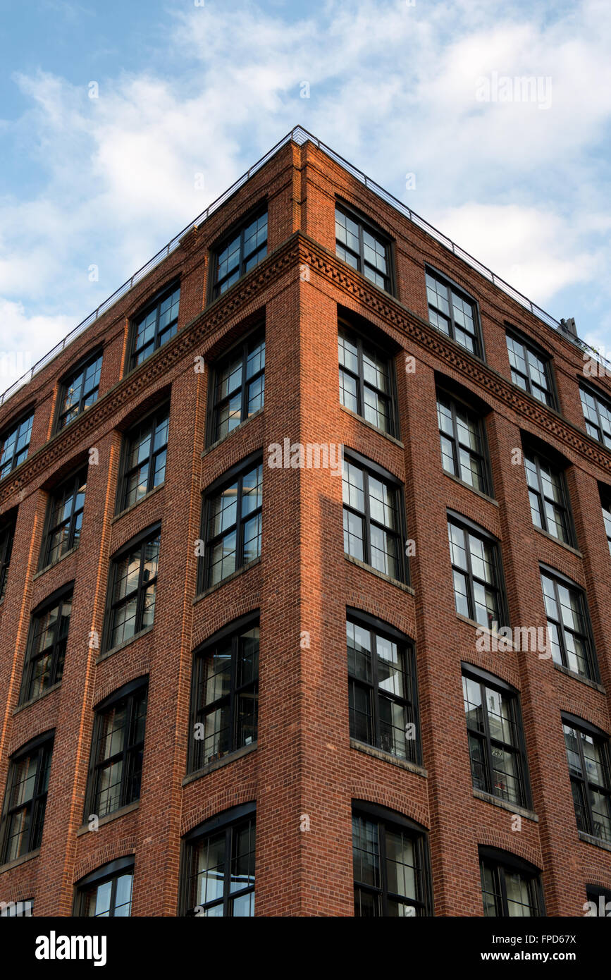 Nice Low Angle View Of Tall Brick Apartment Building With Beautiful Blue Sky And  Clouds Reflecting In Windows