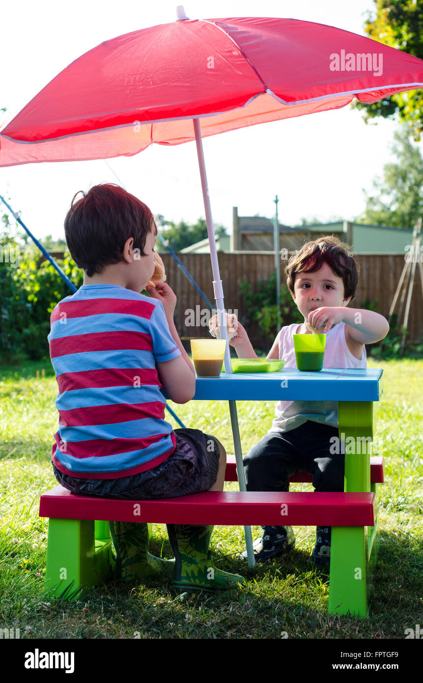 two-young-boys-enjoy-a-picnic-in-their-back-garden-FPTGF9.jpg
