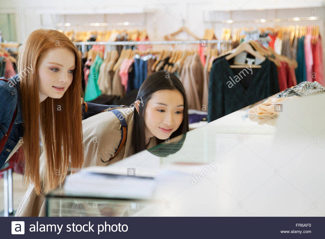 girlfriends shopping in trendy clothing store - Stock Image