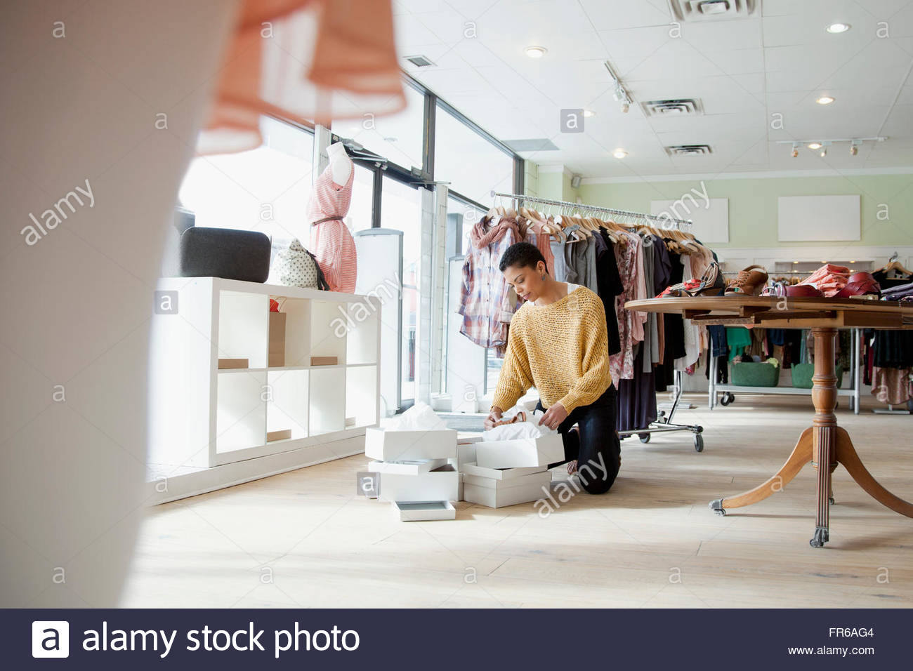 store owner organizing merchandise - Stock Image