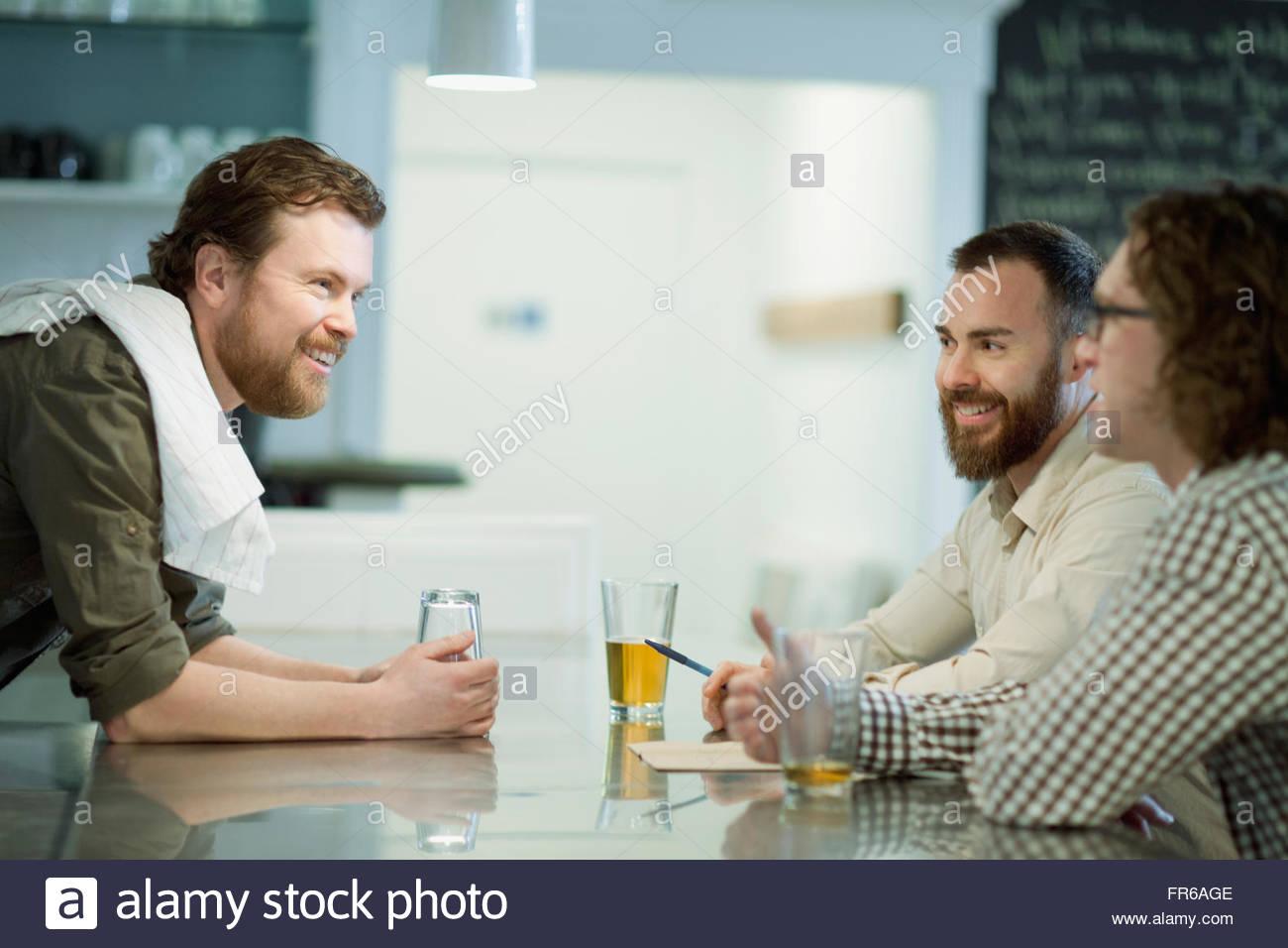 patrons enjoying drinks at diner - Stock Image