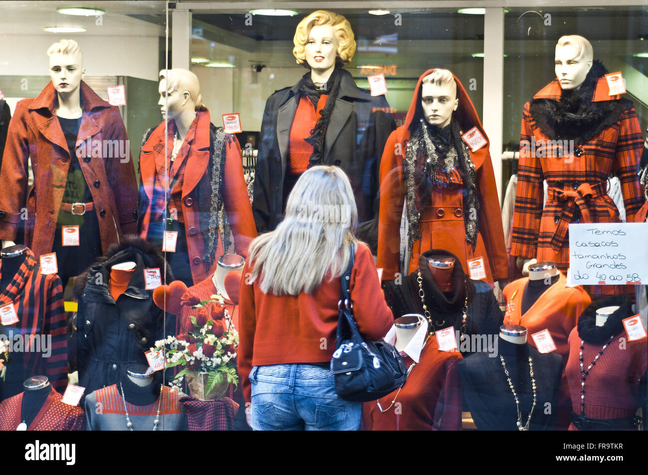 Consumer observes coats for winter showcase store installed in the city center - Stock Image