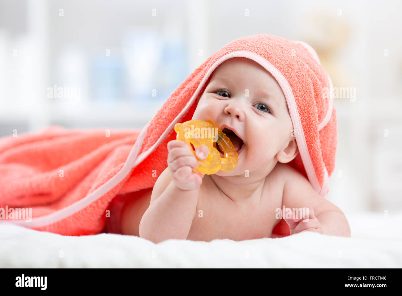 Cute baby with teether under a hooded towel after bath - Stock Image