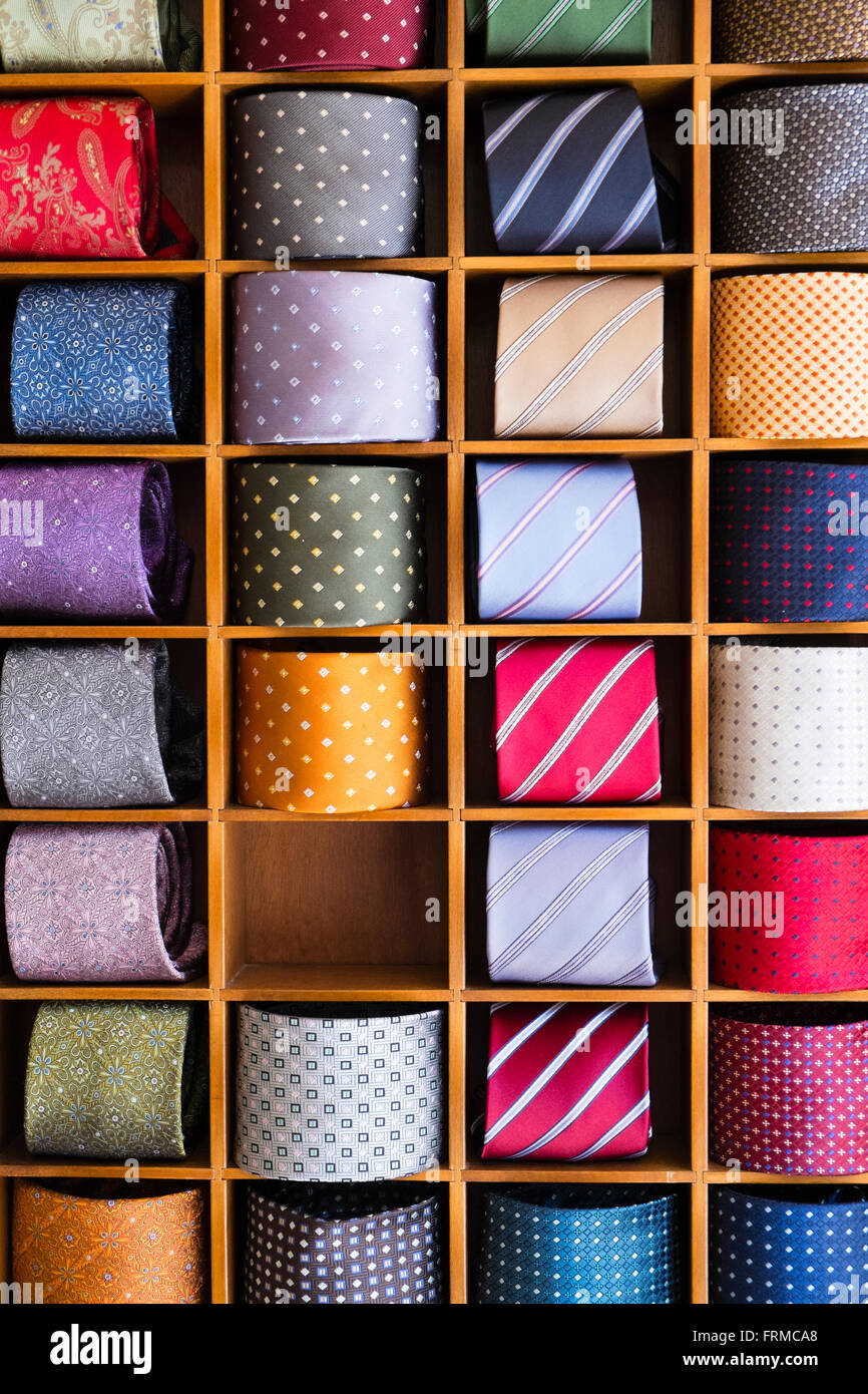 Display of colourful mens' ties, rolled and set between wooden partitions, one compartment empty. Stock Photo