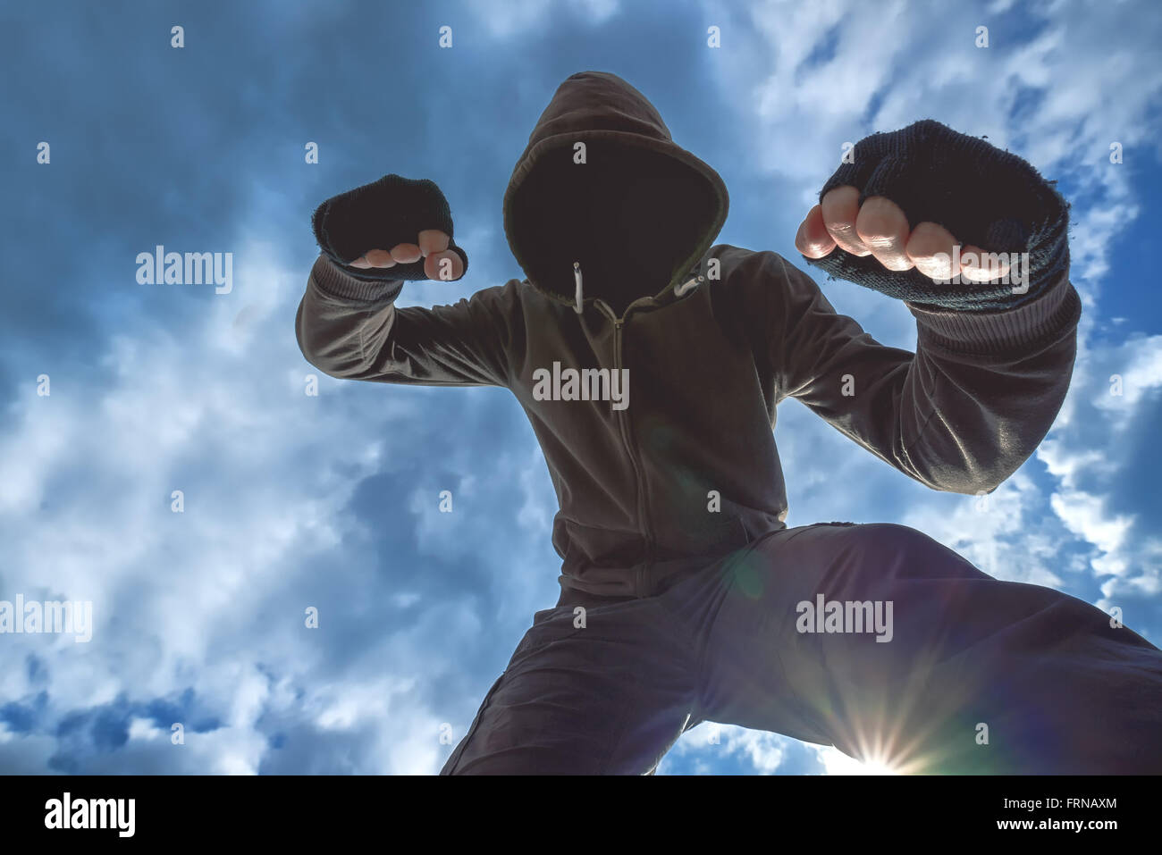 Violent attack, unrecognizable hooded male criminal kicking and punching victim on the street. - Stock Image