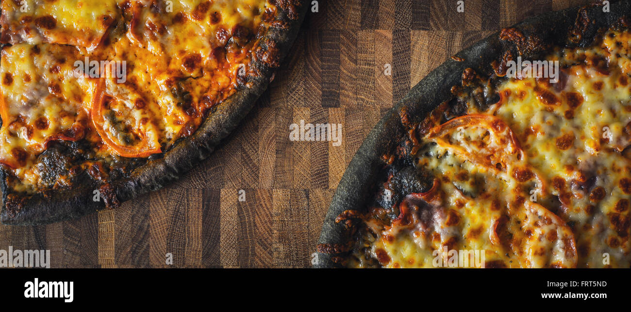 Dough black pizza on the wooden table wide screen - Stock Image