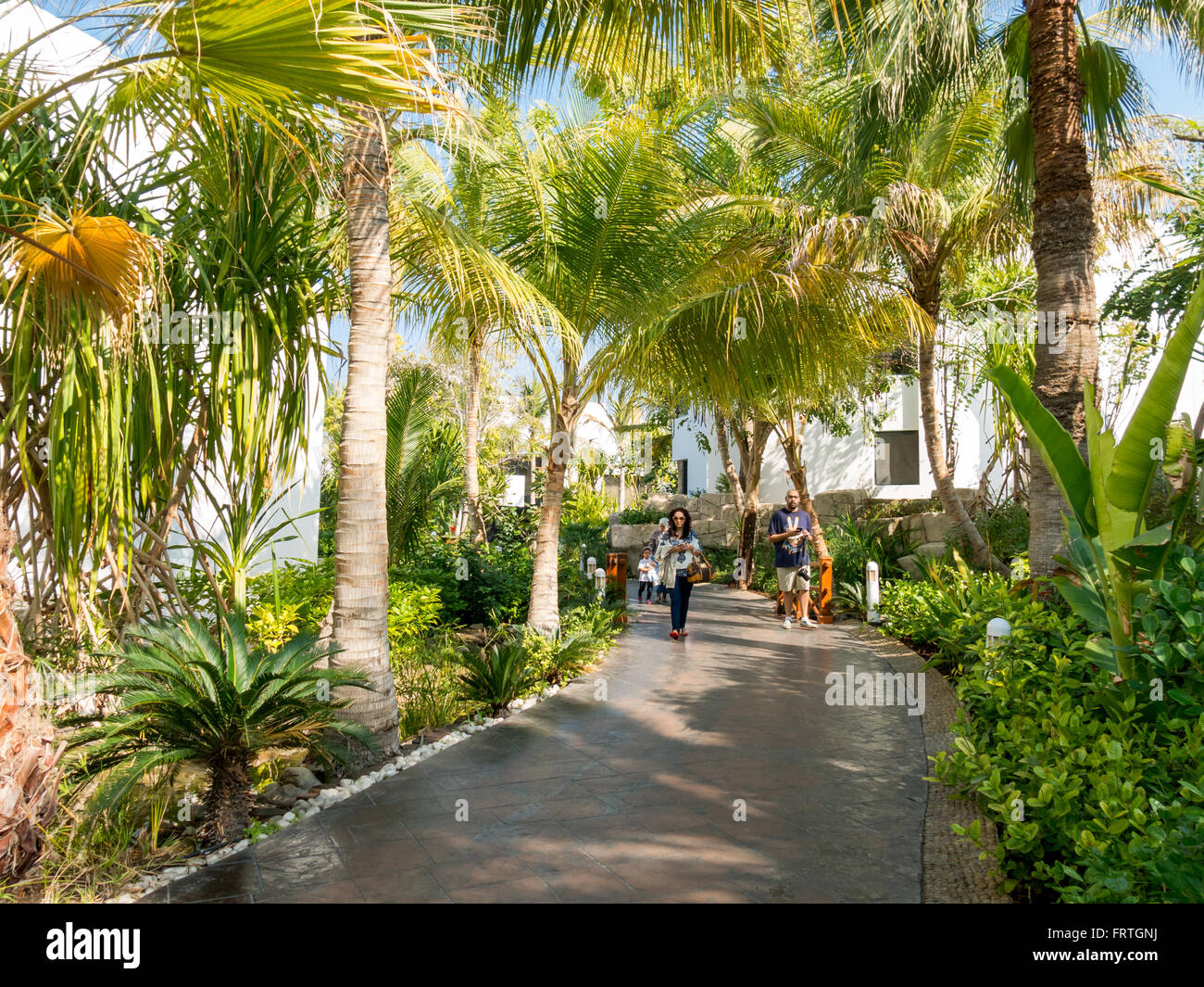 People walking in tropical garden of luxury hotel beach resort in ...