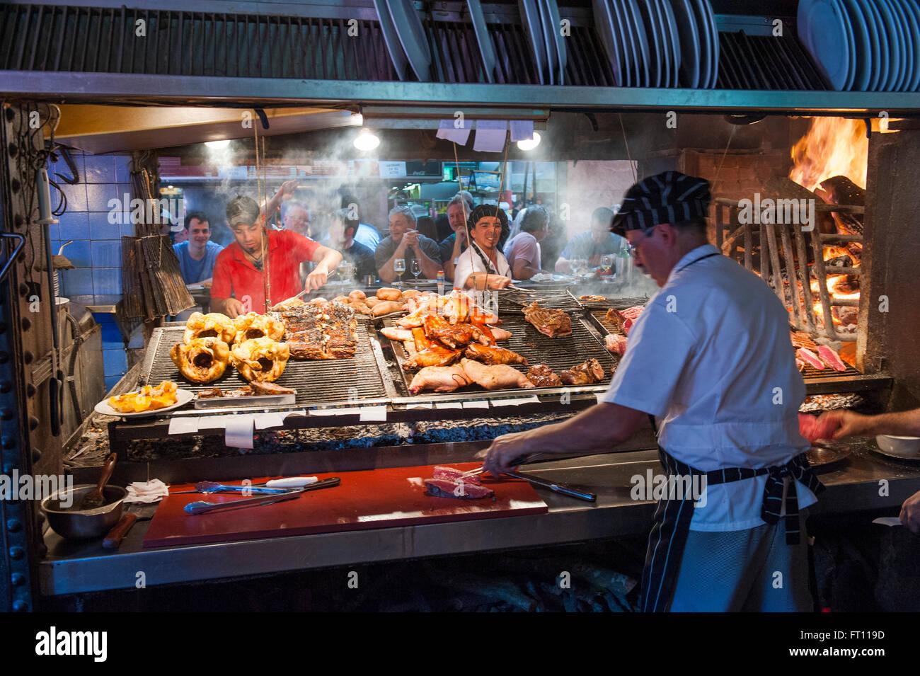 Cooks preparing steak and meat, Parilla type restaurant, Mercado del Puerto, Montevideo, Montevideo, Uruguay - Stock Image