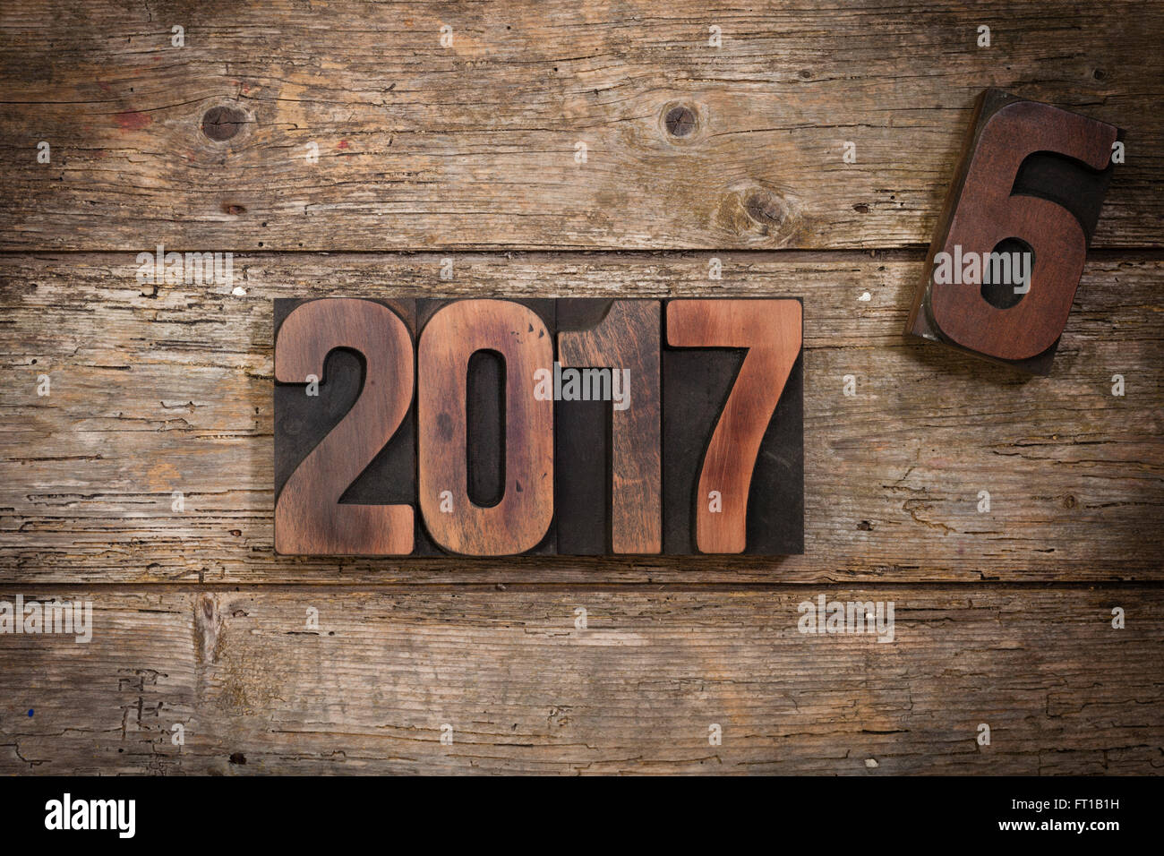 Turn of  the year 2016 to 2017 depicted with vintage letterpress printing block numbers on rustic wooden background - Stock Image