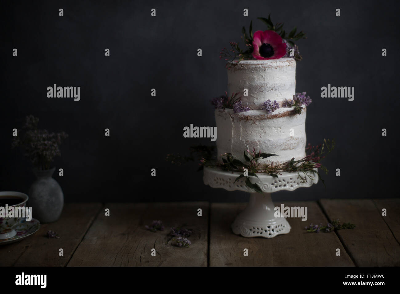 Homemade cake, flower decorated, on a stand. Dark background. - Stock Image