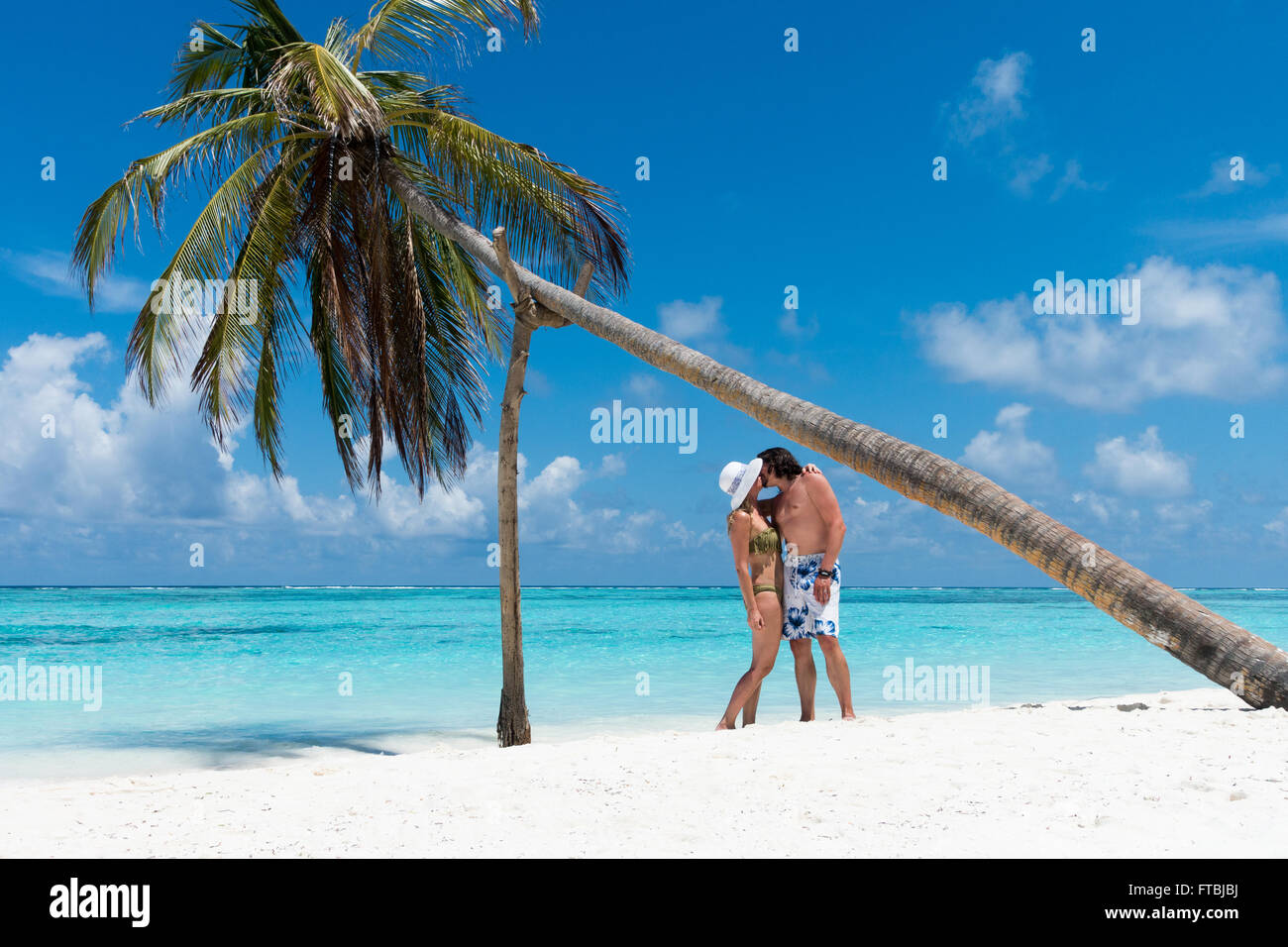 man and woman kissing under a leaning palm tree on a white sand
