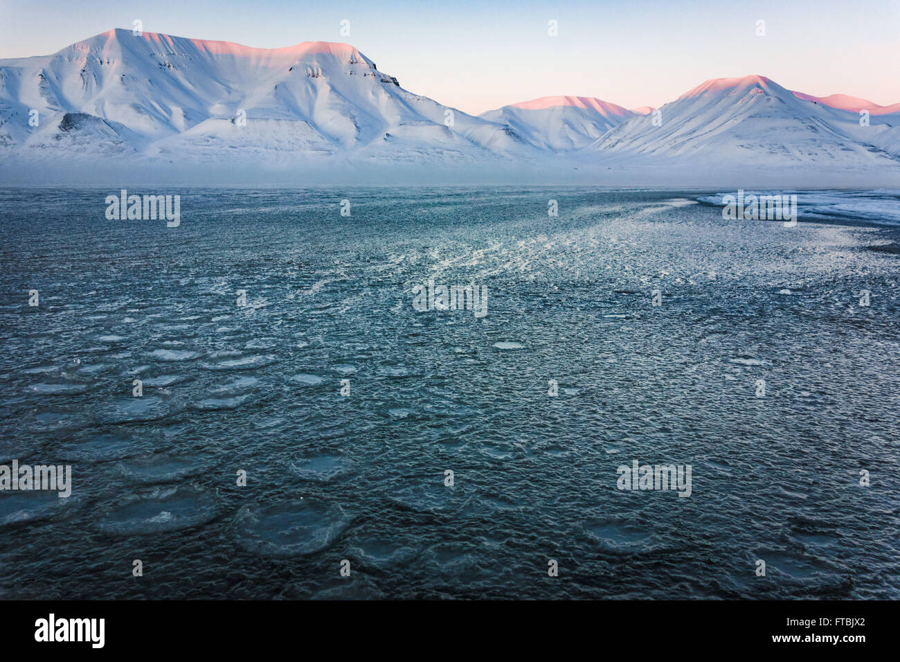 Sunset frozen shoreline at Sjøskrenten beach with views to Hiorthfjellet, Longyearbyen, Spitsbergen, Svalbard. - Stock Image