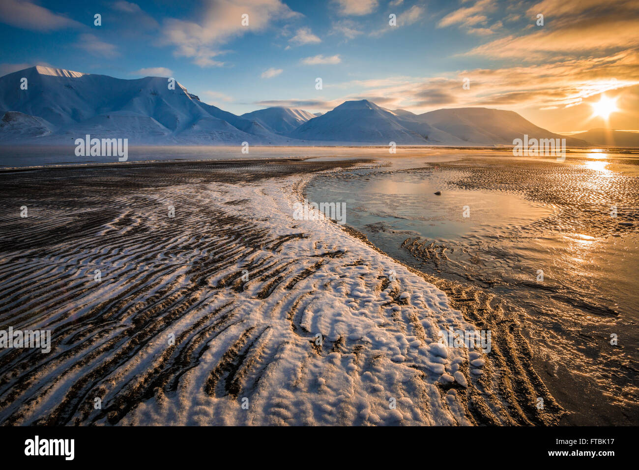 Sunrise ice formations on Sjøskrenten beach with views to Hiorthfjellet, Longyearbyen, Spitsbergen, Svalbard. - Stock Image