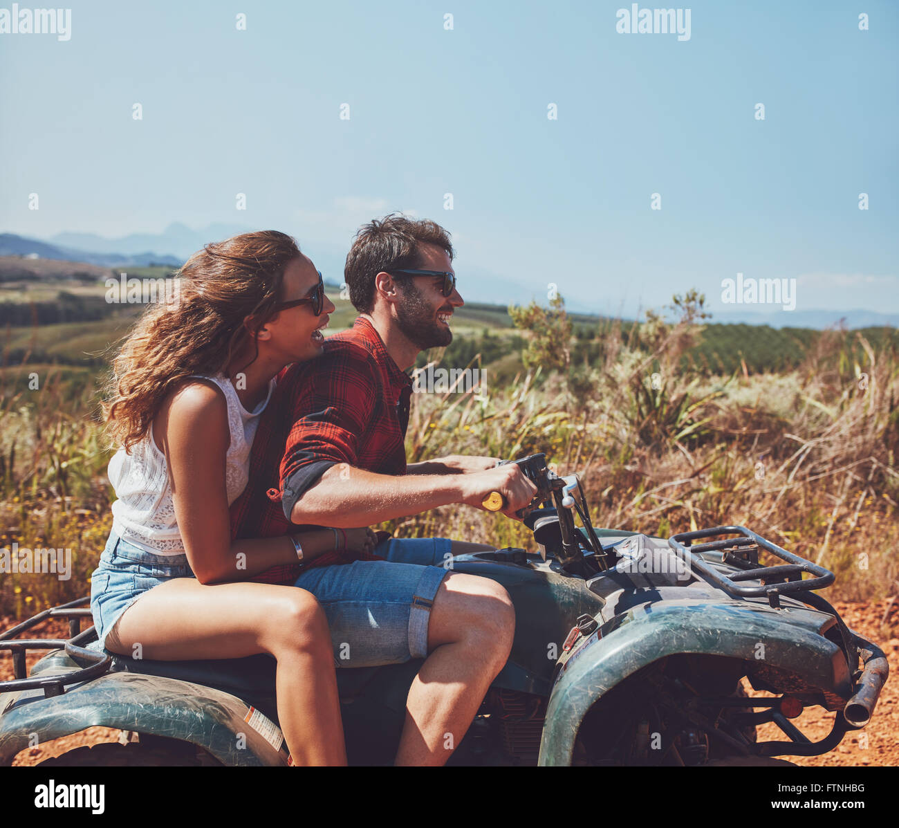 Side view of young man and woman riding on a quad bike on a summer holiday. Couple enjoying holidays on a quad bike - Stock Image