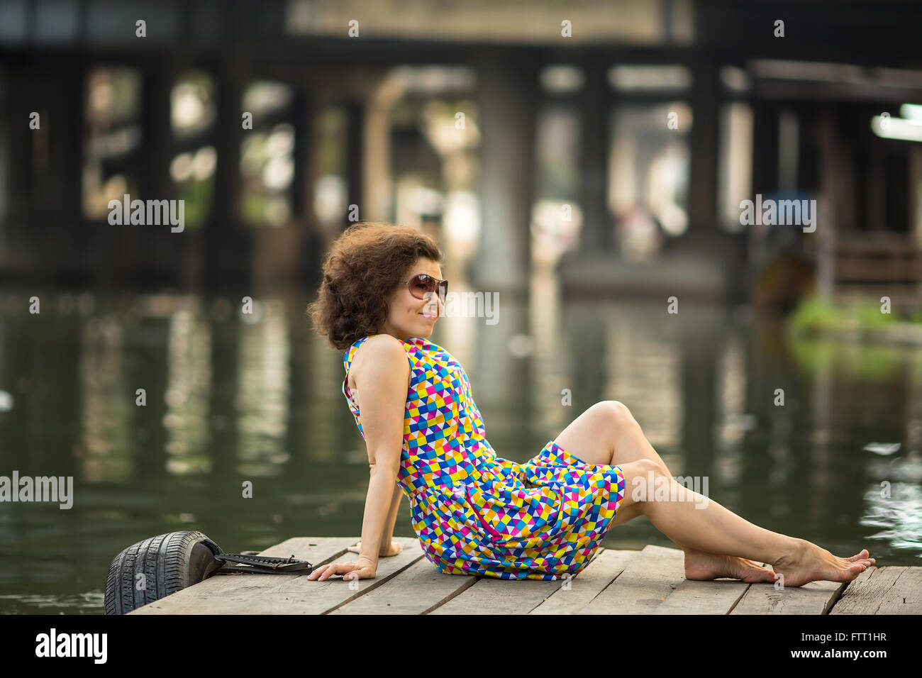 Fashionable young asian woman in sunglasses sitting on wooden river embankment. - Stock Image