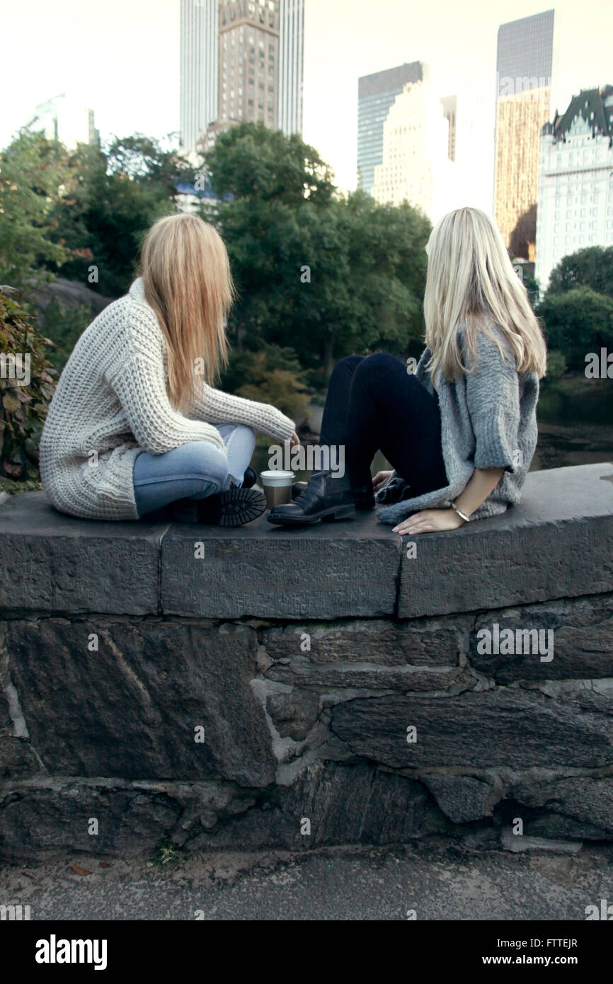 Two young women sitting in Central Park in the fall - Stock Image