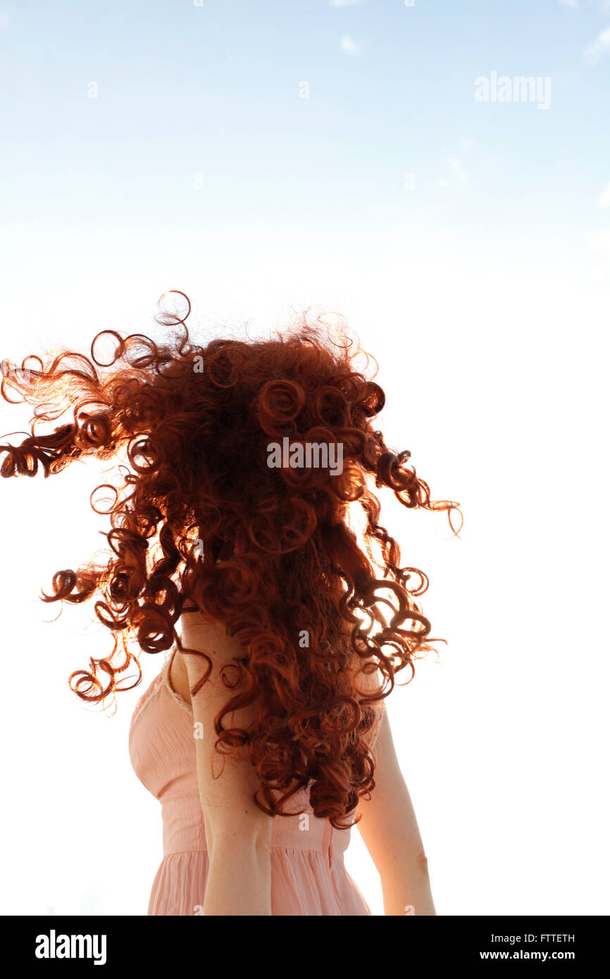 Curly redhead woman turning - Stock Image