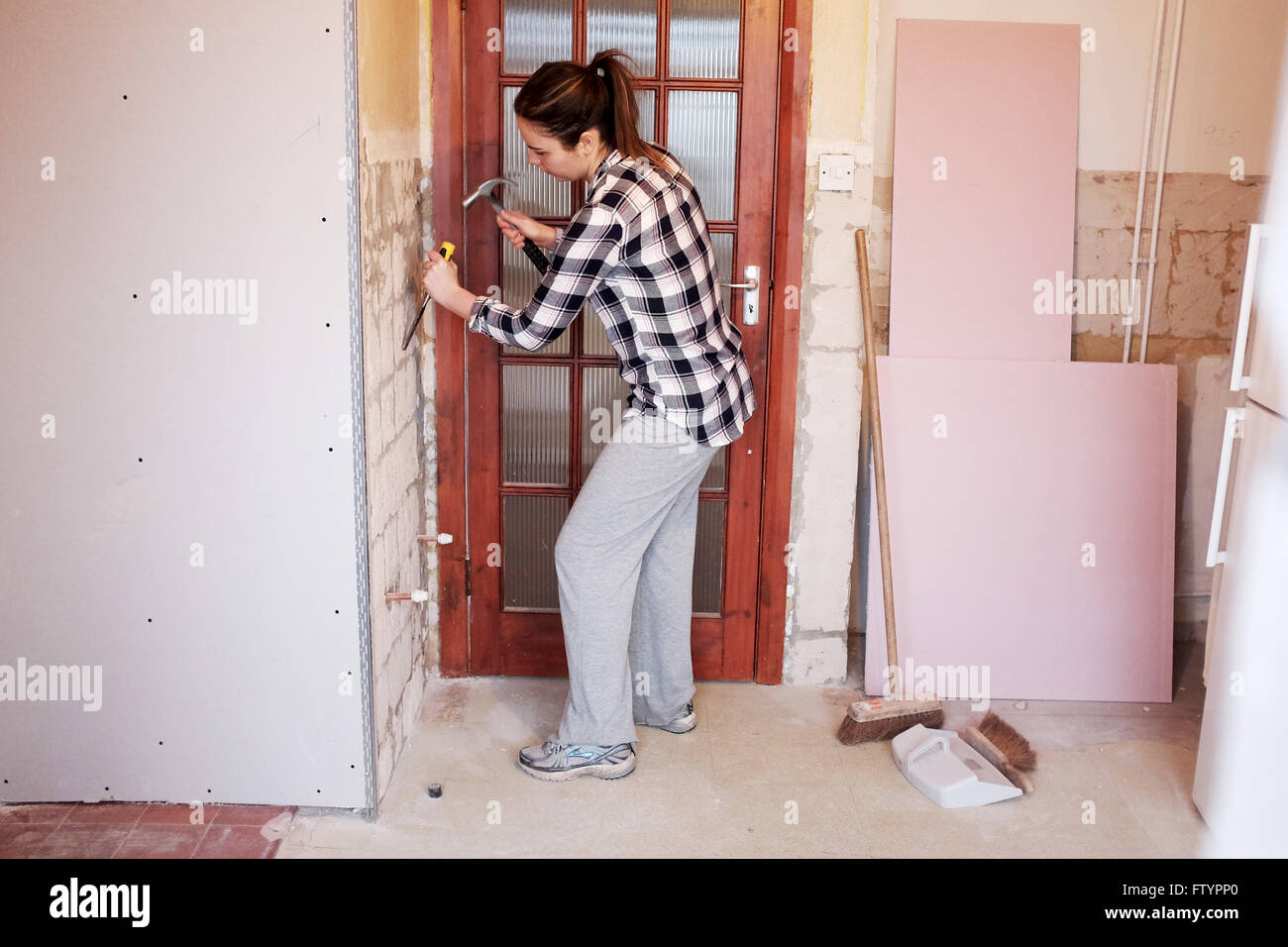 Awesome Young Woman With Hammer And Chisel Taking Off Wall Tiles In Kitchen In Her  20s Doing DIY At Her Bungalow Home