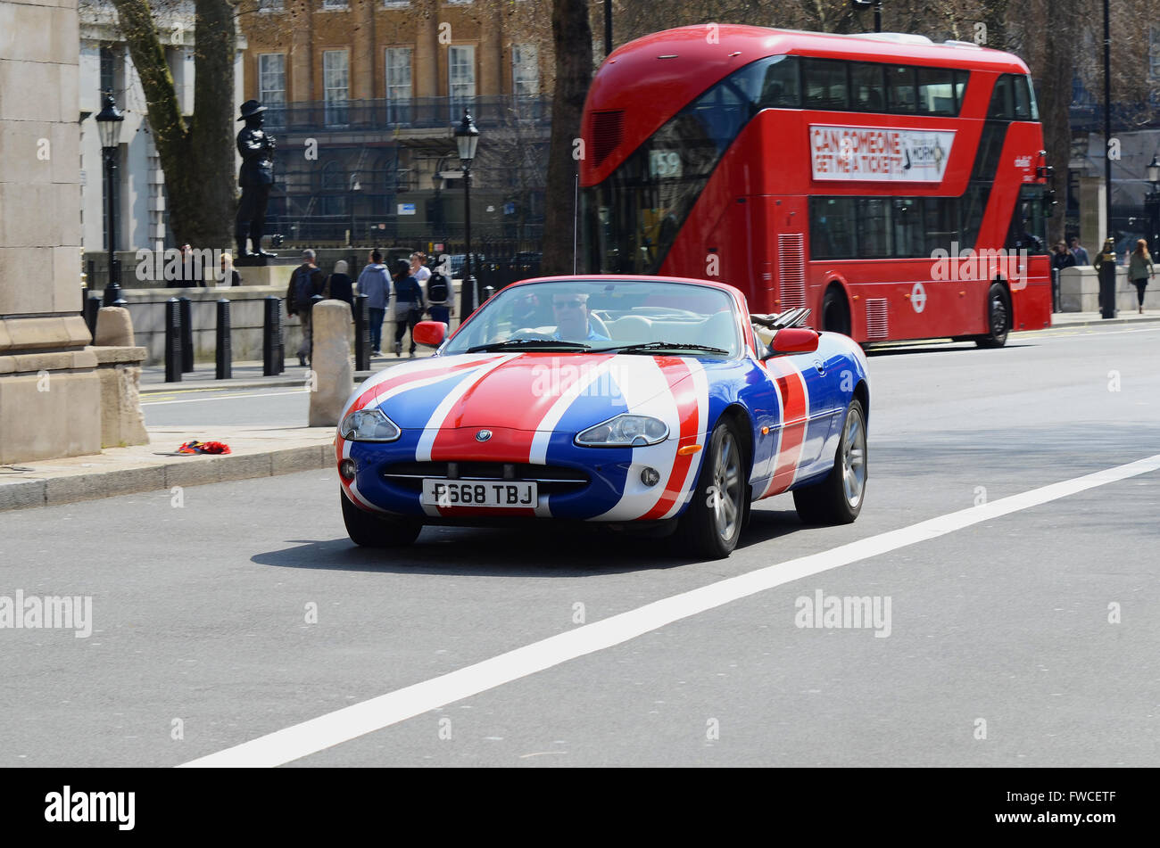 an-open-top-jaguar-xk8-in-union-flag-colour-scheme-driving-through-FWCETF.jpg