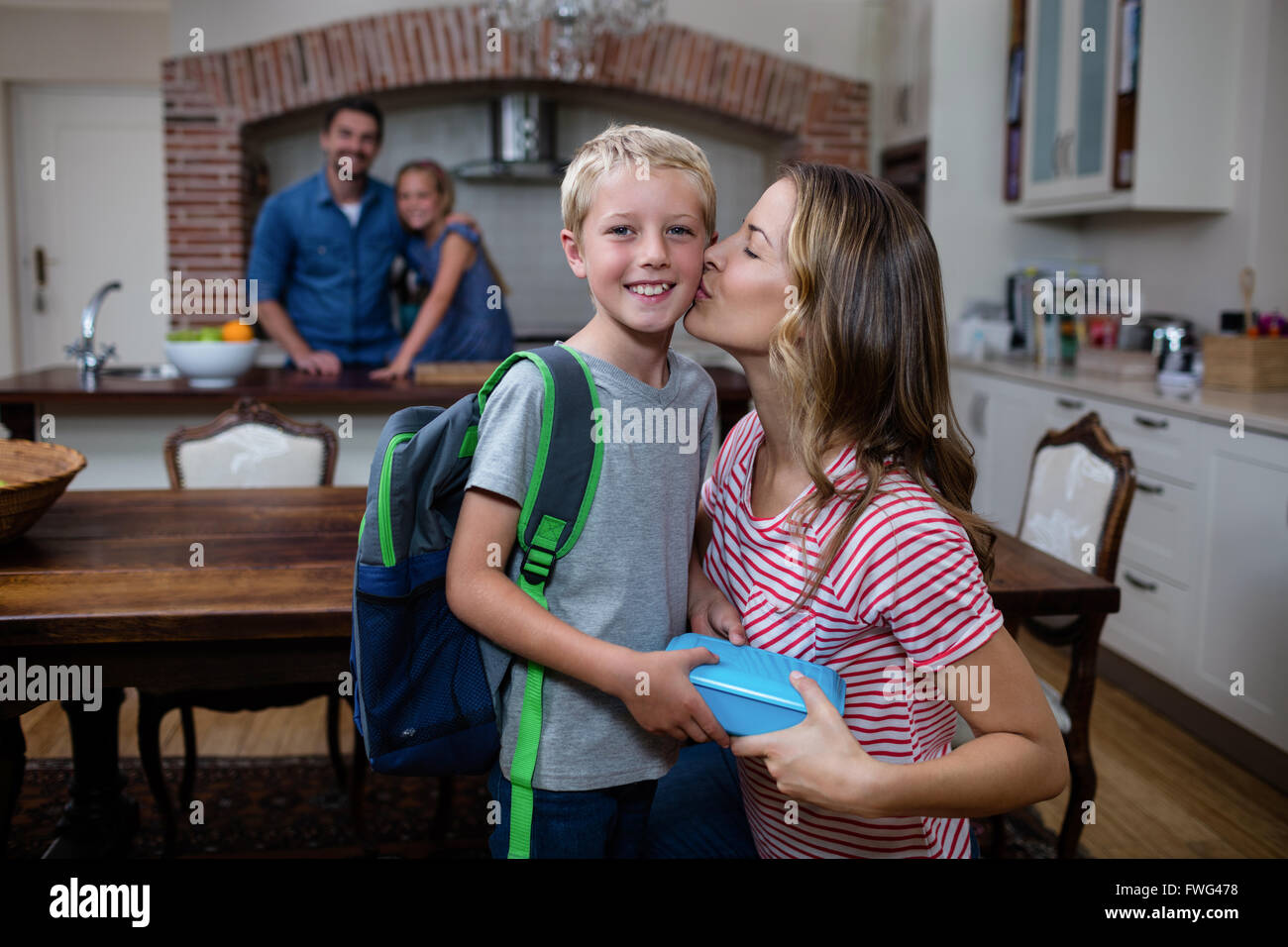 Mother kissing his son while giving him a school lunch box Stock Photo