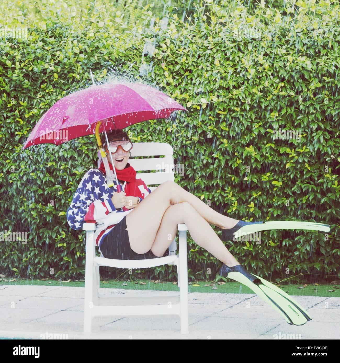 Woman holding umbrella in rain - Stock Image