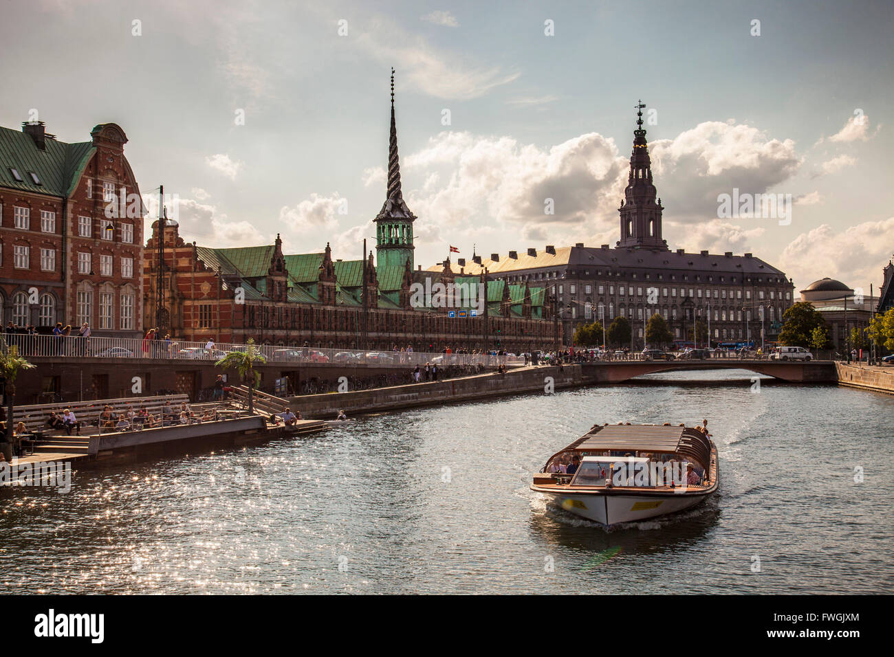 Ferry On River By Borsen Building And Christiansborg Palace Against Cloudy Sky - Stock Image