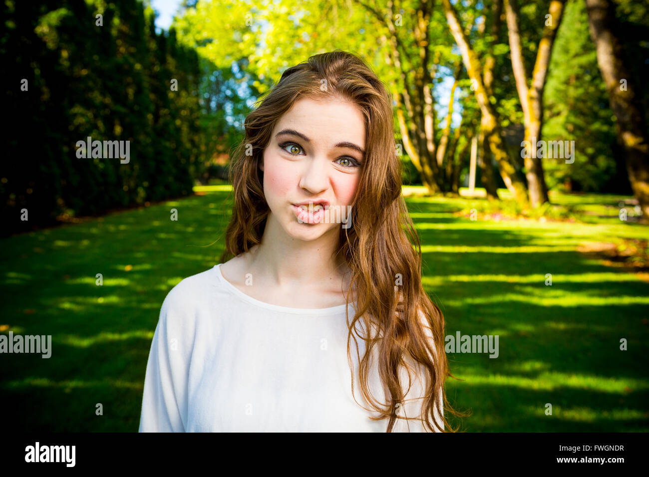 A beautiful young girl poses for a fashion style portrait outdoors at a park with natural lighting. - Stock Image