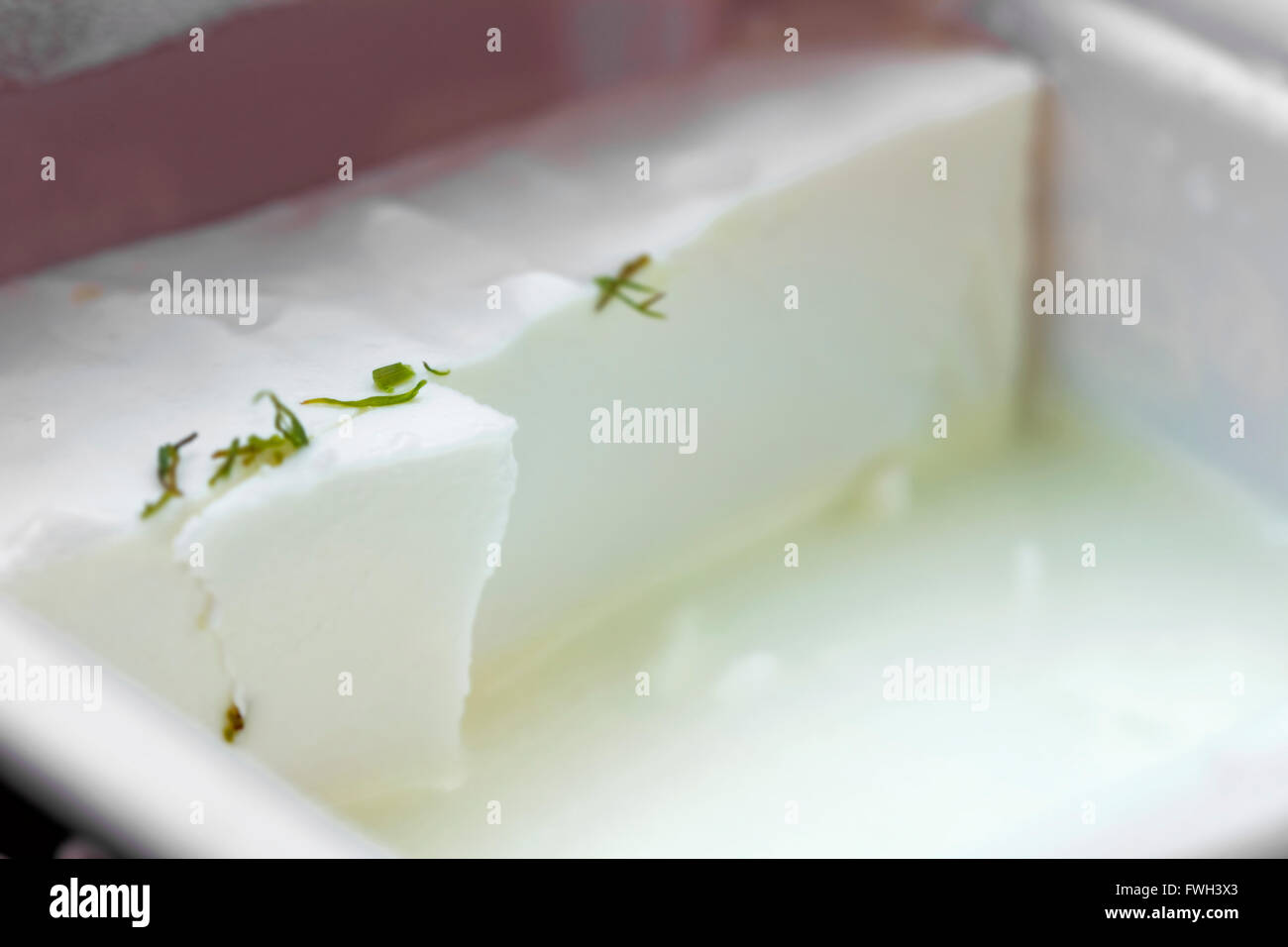 Fresh piece of white cheese in box - Stock Image