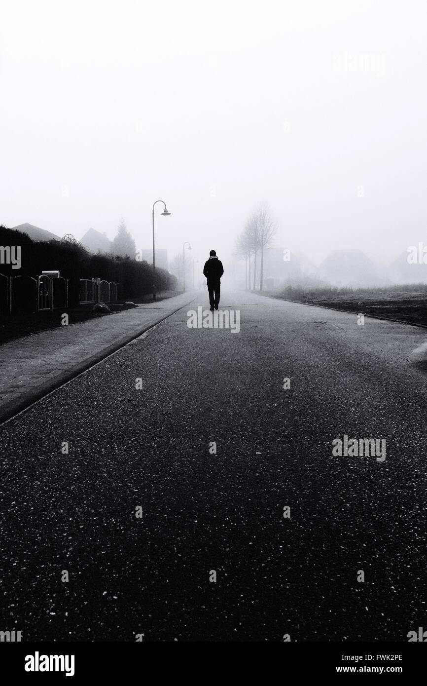 Silhouette Person Walking On Road - Stock Image