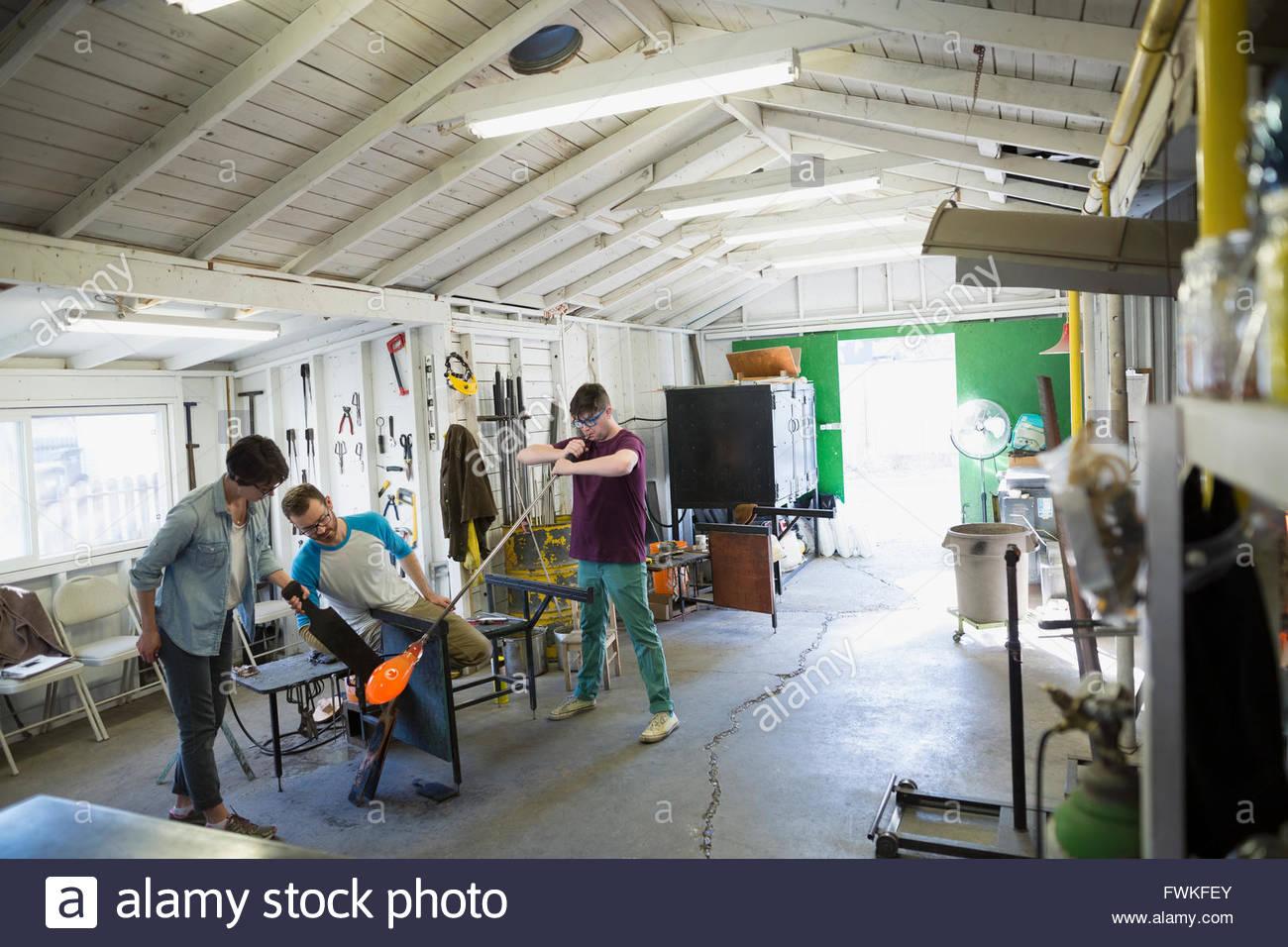 Glassblowers blowing molten glass in workshop - Stock Image