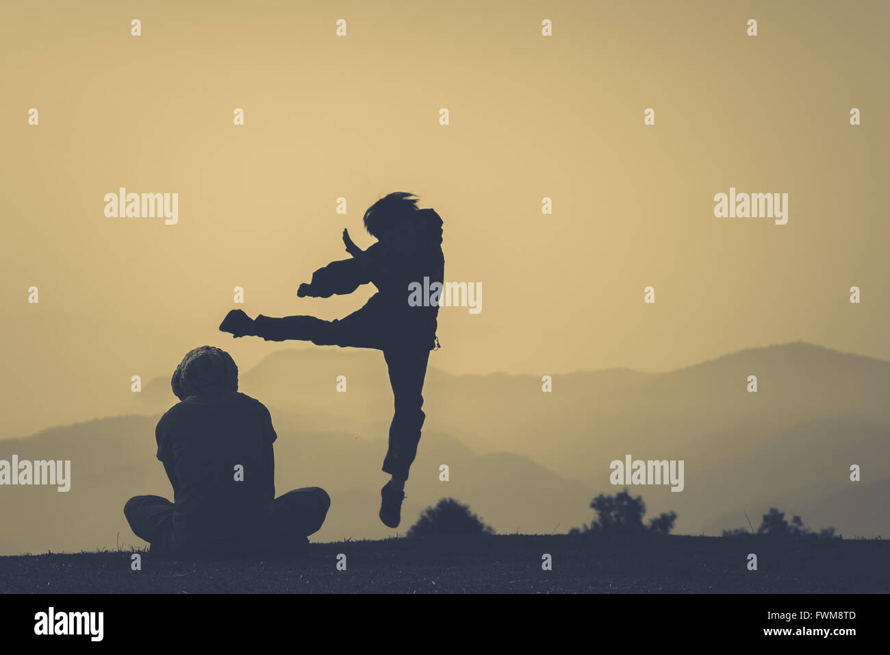 Silhouette Person Exercising By Friend On Field - Stock Image