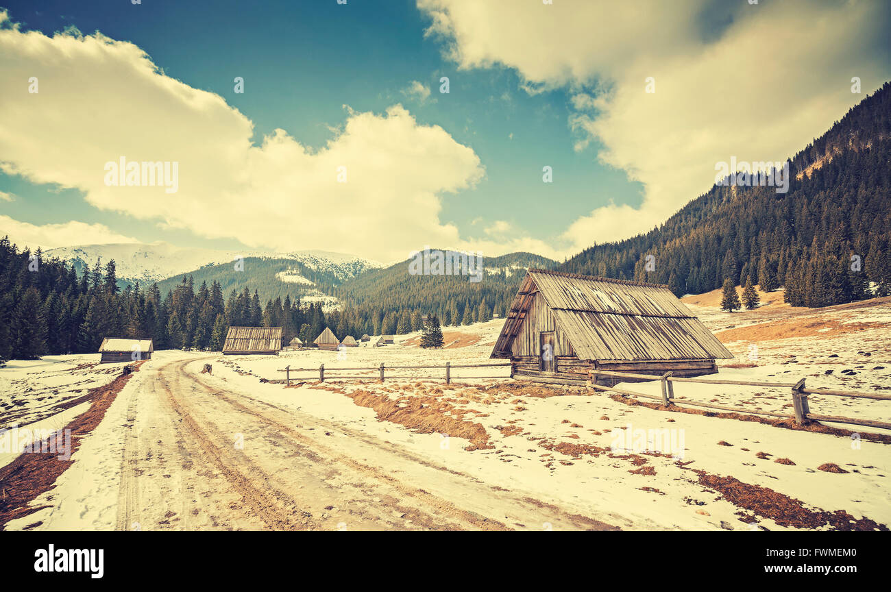 Vintage toned wooden huts by a road in Tatra Mountains, end of winter and beginning of spring, Poland. - Stock Image