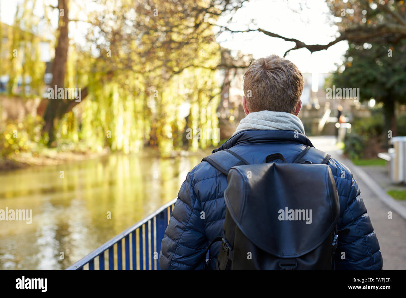 Rear View Of Young Man Walking By River In City - Stock Image