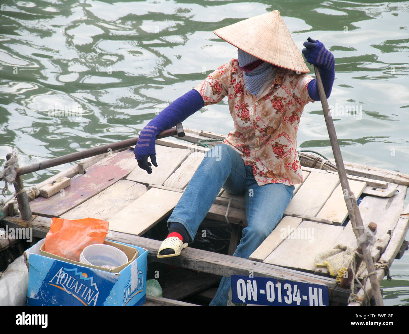A woman sitting at the back of a wooden row boat. Stock Photo