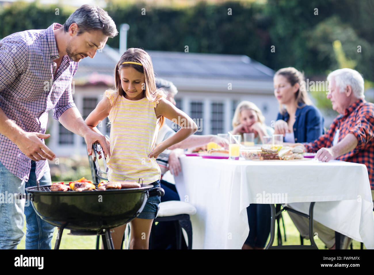 Father and daughter at barbecue grill while family having lunch in background Stock Photo