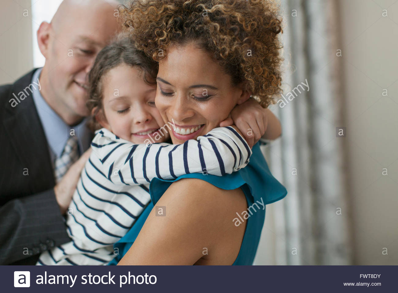 Young daughter hugging mother affectionately. - Stock Image