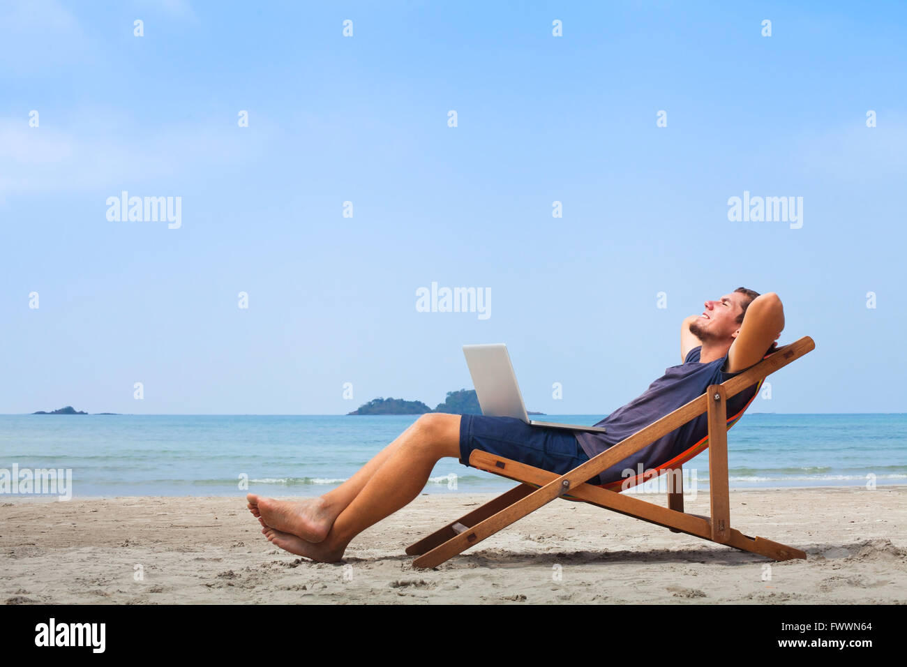 freelancer, happy successful businessman with laptop on the beach, blue sky - Stock Image
