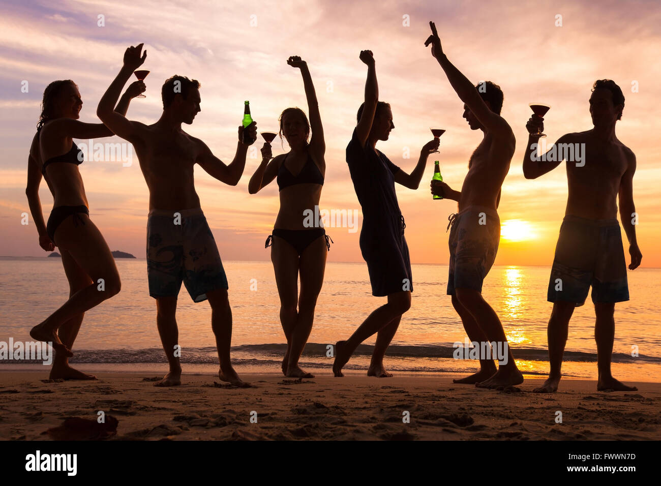 beach party, group of young people dancing, friends drinking beer and cocktails at sunset - Stock Image