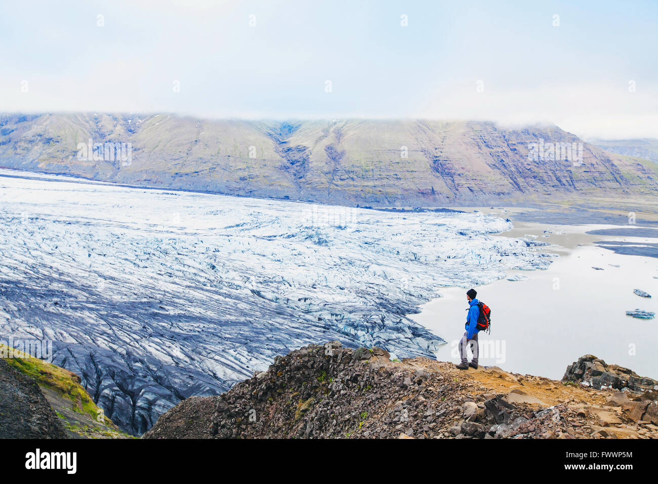 traveler enjoying panoramic view of glacier in Iceland - Stock Image