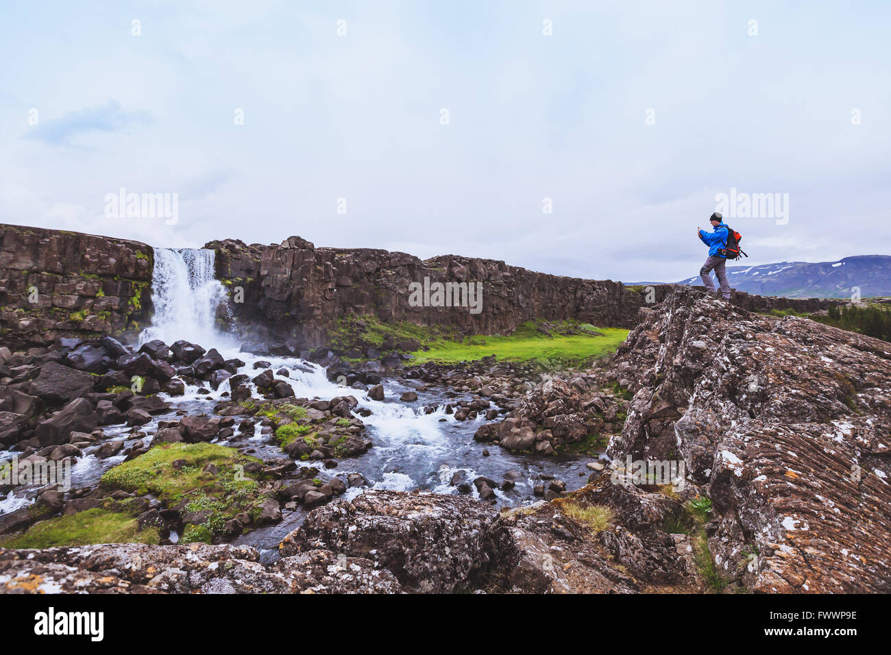 backpacker traveler taking photo of waterfall with mobile phone - Stock Image
