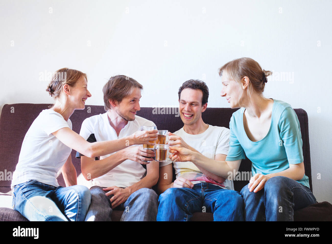group of friends cheering at home, happy young smiling people with drinks, copyspace - Stock Image