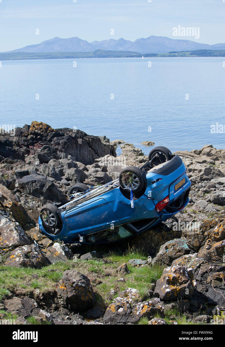 An overturned car crashed on rocks by the sea. - Stock Image